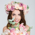 Cute lovely cheerful young female in beautiful rose wreath showing bouquet of flowers